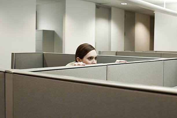 woman hiding behind cubicle in office - fear stock photos and pictures
