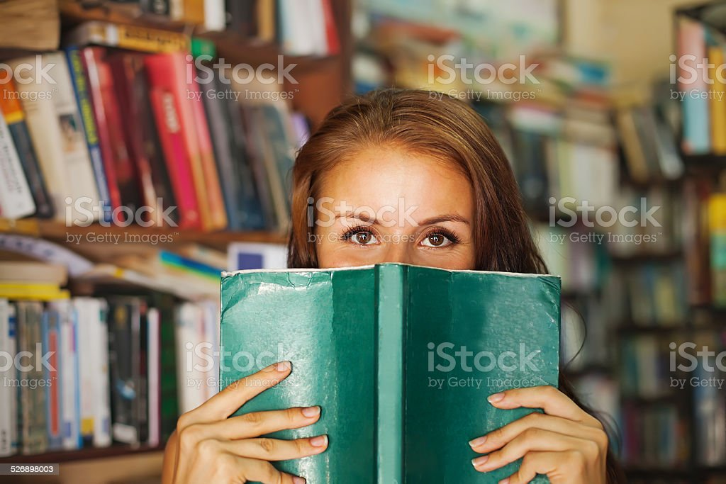 Woman hiding behind the green book stock photo