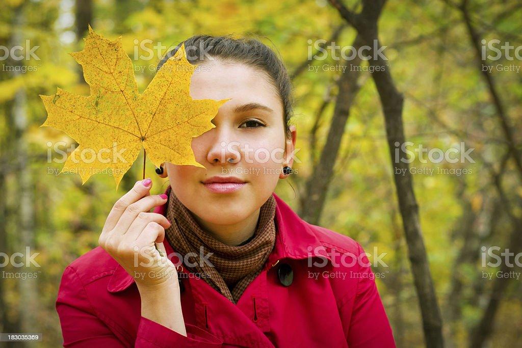 Woman hiding eye behind yellow maple leaf royalty-free stock photo