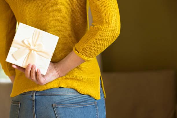 frau, geschenk-box hinter ihrem rücken versteckt - originelle geburtstagsgeschenke stock-fotos und bilder