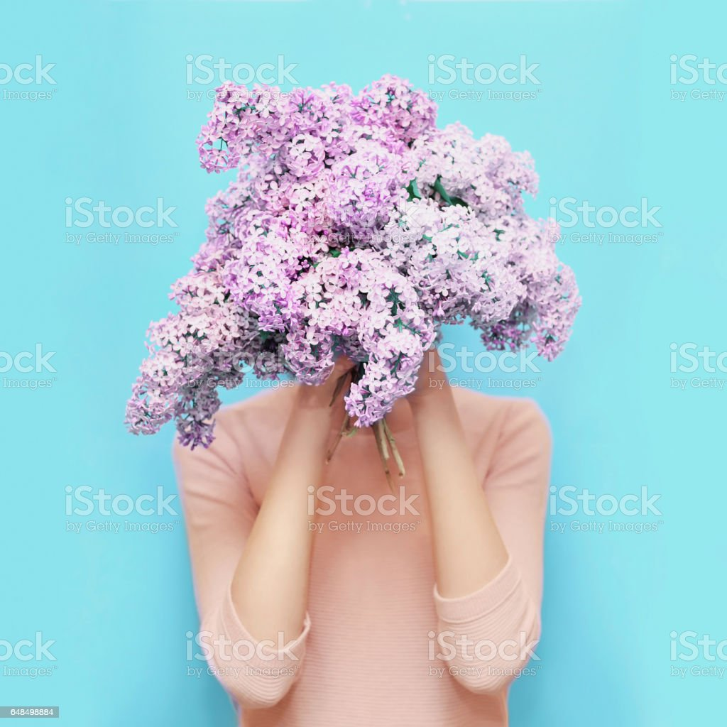Woman hiding head bouquet lilac flowers over colorful blue background stock photo