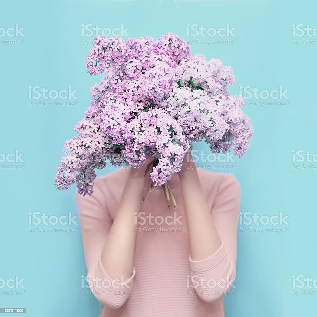 Woman hiding head in bouquet lilac flowers over colorful blue stock photo