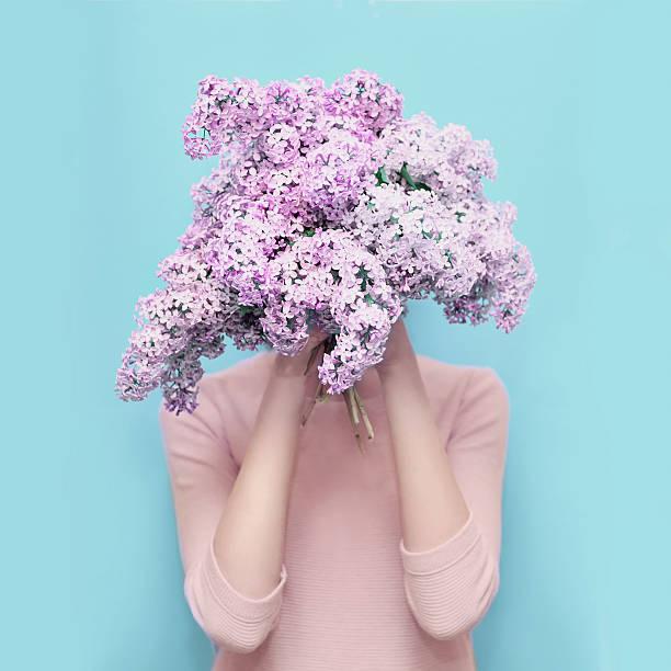 カラフルなブルーの花束にライラックの花で頭を隠す女 - 春のファッション ストックフォトと画像