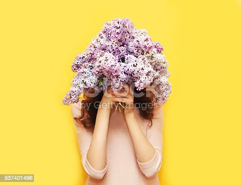 istock Woman hiding head in bouquet lilac flowers over yellow background 537401496