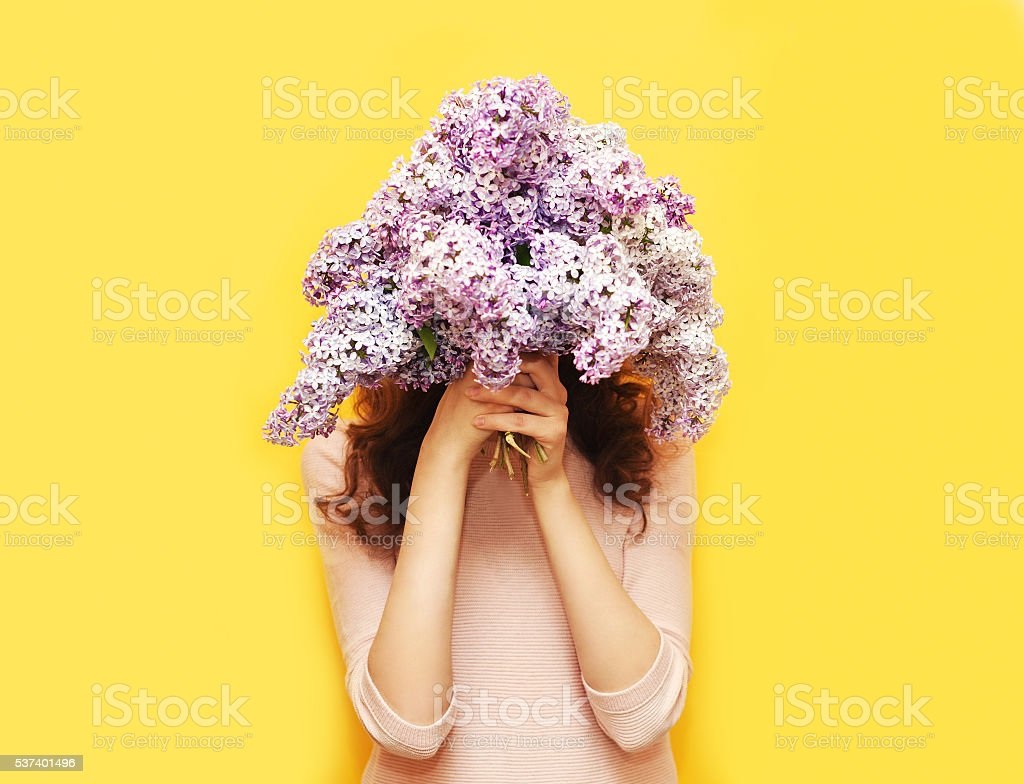Woman hiding head in bouquet lilac flowers over yellow background stock photo
