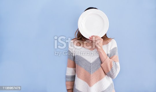 Shot of a woman hiding her face behind a plate against blue background