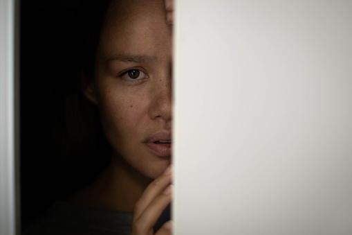 Frightened woman hiding behind a closet door
