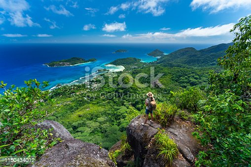 female hiker woman tourist standing high above indian ocean on tropical island of seychelles mahe enjoying amazing view