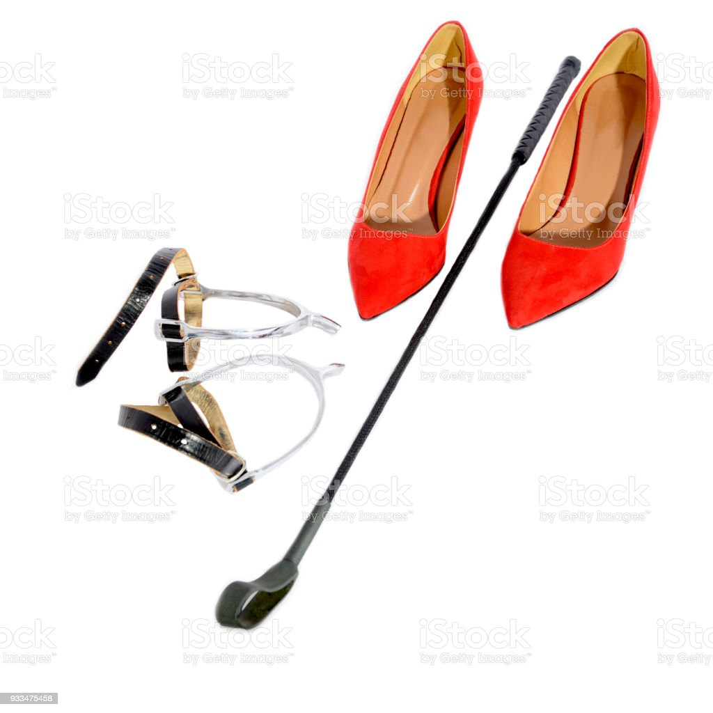 Woman high heels red shoes with spurs and riding crop stock photo