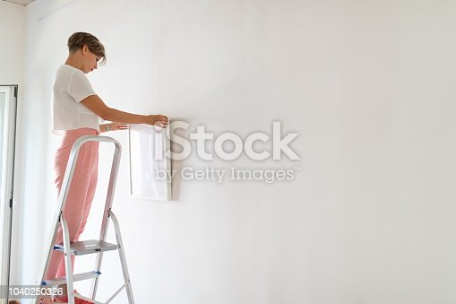 508897972 istock photo Woman high on the ladder hanging painting 1040250326
