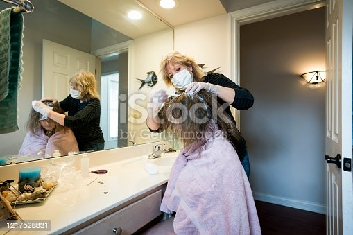 Woman wearing a face mask and gloves during the corona virus pandemic applies highlighting chemicals to her teenage daughter's hair at home in the bathroom.