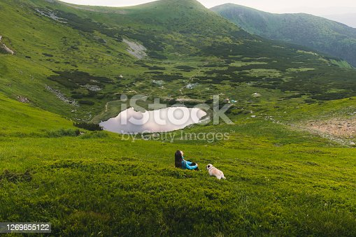 Young woman traveler and her small dog - pug breed relaxing after the hiking trip in the mountains on the grass meadow looking at the scenic lake during summer sunset