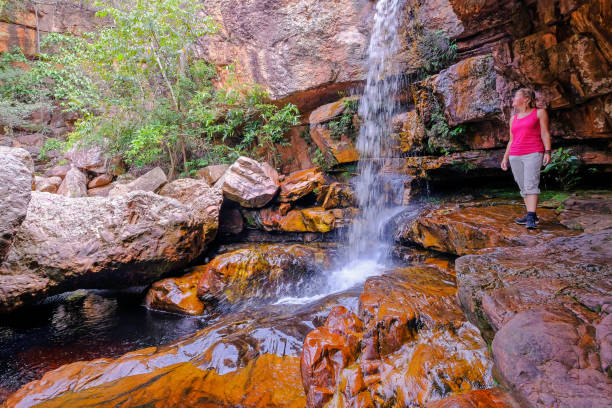 Woman hiker at Cachoeira Da Primavera, Spring Waterfall, Rio Lencois river, Chapada Diamantina National Park, Brazil stock photo