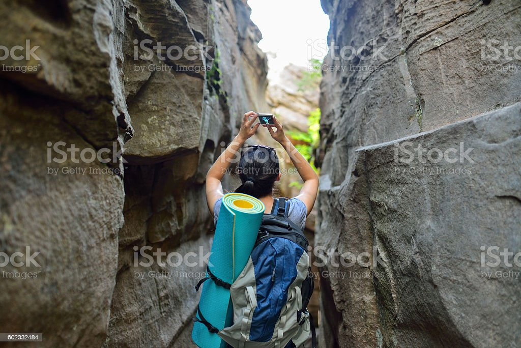 Woman Hiker Backpacker exploring narrow canyon in summer day and - foto de stock