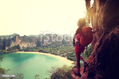 istock woman hiker enjoy the view at sunrise mountain peak cliff 596067396