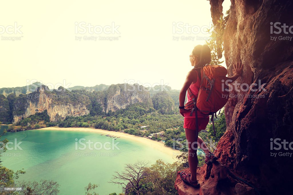 woman hiker enjoy the view at sunrise mountain peak cliff stock photo