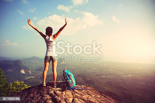 istock woman hiker enjoy the view on mountain peak cliff 507869286