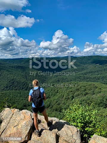 Mathias, West Virginia, USA - August 24, 2019.  A woman takes a break from an early morning hike in the Lost River State Park to enjoy the scenic view.