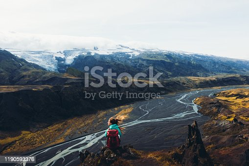 Young woman backpacker getting to the top of the mountains and looking at scenic view of Icelandic nature in Thorsmork valley