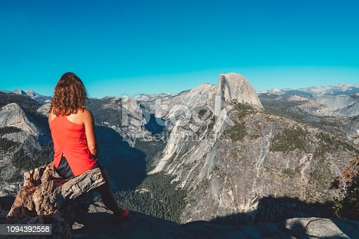 Young woman hiking in Yosemite national park. Enjoying in the view of half dome. Half Dome is a granite dome at the eastern end of Yosemite Valley in Yosemite National Park. Beautiful scenery surrounding her, majestic mountains rising high up. Summer trip to the USA, visiting plenty of national parks across the country.