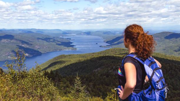Woman Hiker Enjoying view from Black Mountain Summit overlooking Lake George, Adirondacks, New York stock photo