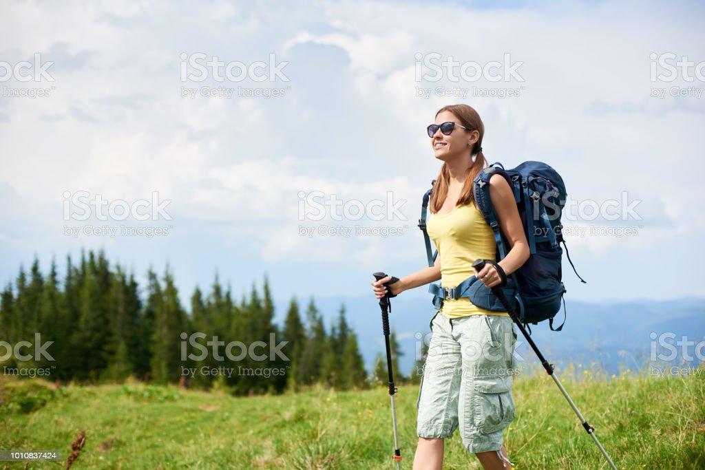 Attractive woman hiker hiking on Carpathian mountain trail, walking...