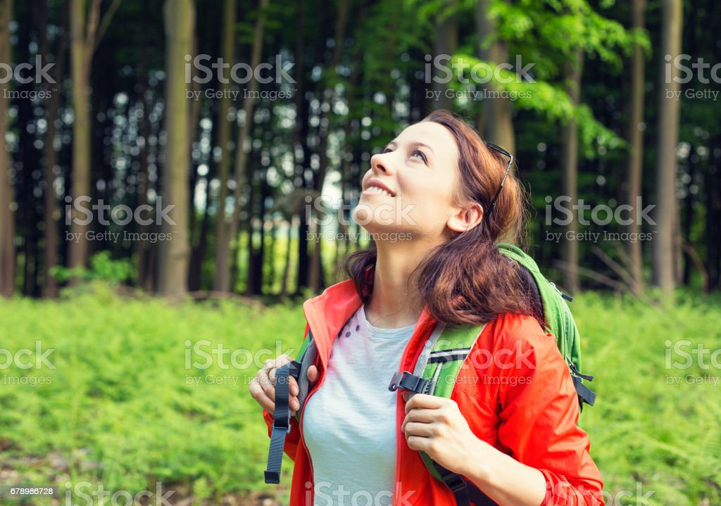 Woman hiker in forest smiling looking up enjoying freedom stock photo