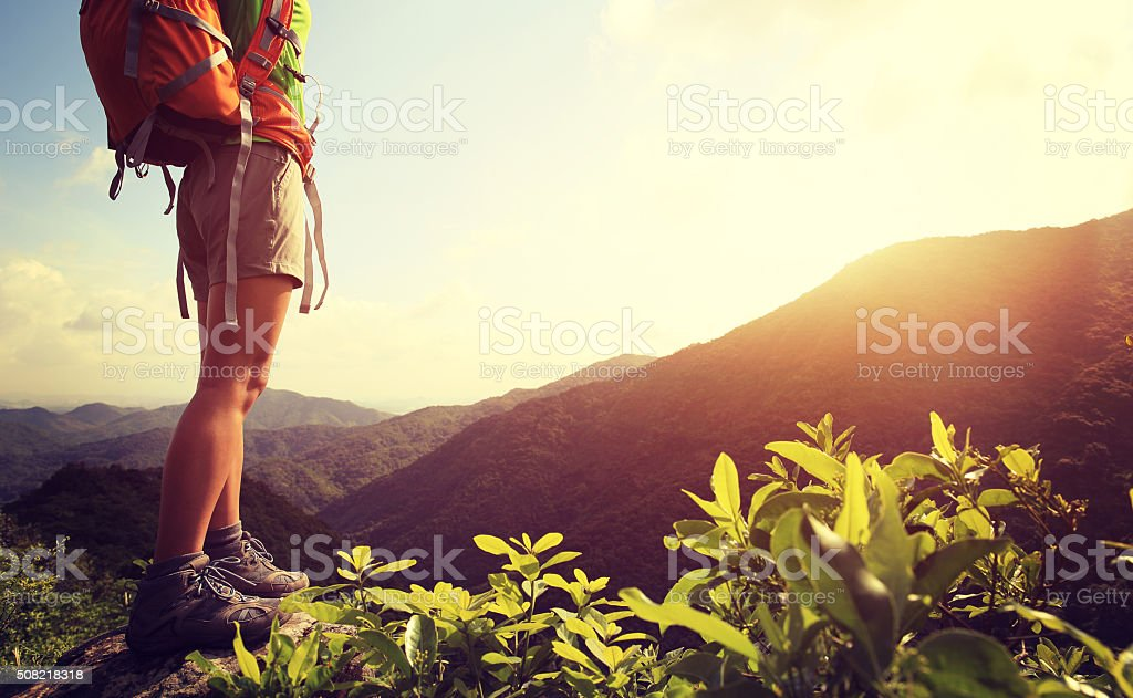 woman hiker legs stand on mountain peak rock stock photo