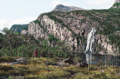 Waterfall on the cliff, water falling into the sea. Raw Scandinavian nature in the autumn time. Waterfall in Norway.