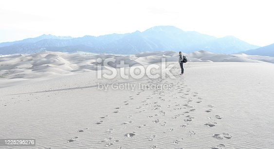 Woman Hiker Looks Back From Blown Out Sky over sand dunes