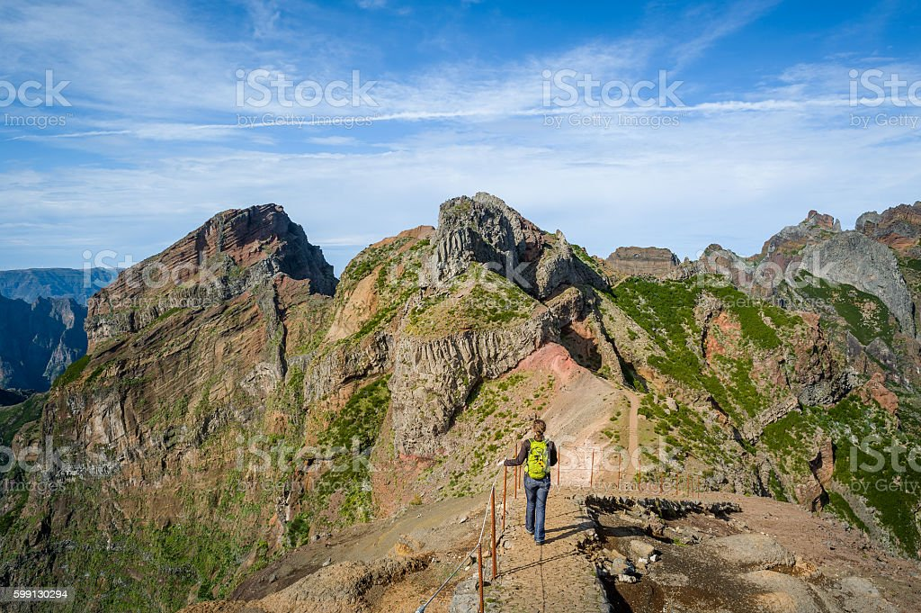 Woman hiker on the dangerous path between the rocky cliffs stock photo