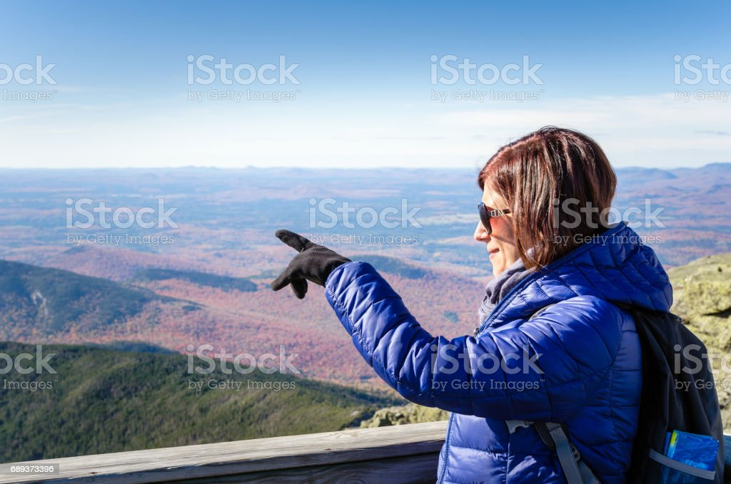 Woman Hiker on the Top of a Mountain Pointing at the Scenery stock photo