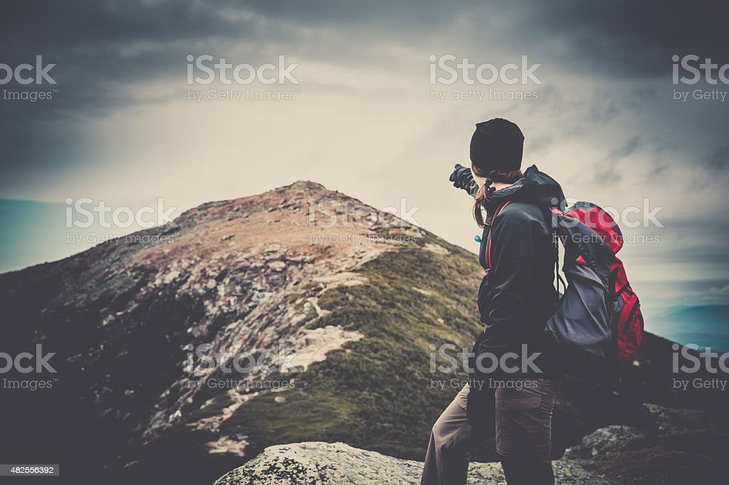 Woman Hiker Pointing at Mountain Summit stock photo