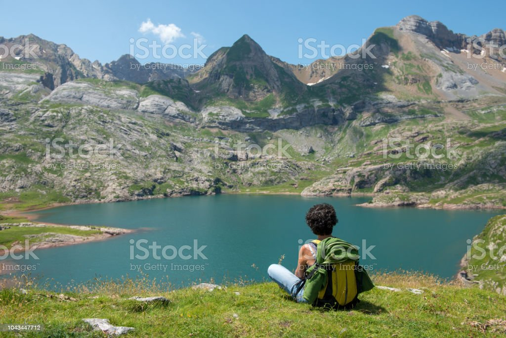 woman hiker resting and  looking at lake in the Pyrenees mountains a woman hiker resting and  looking at lake in the Pyrenees mountains Activity Stock Photo