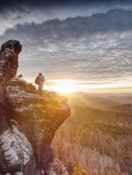 Woman hiker set tripod with camera on exposed rocky summit stock photo