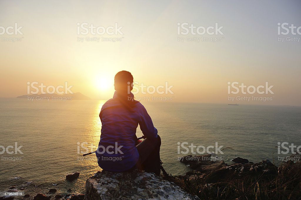 woman hiker sit on rock face the sunrise stock photo