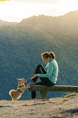 istock Woman hiker sitting on bench and playing with small dog on top of the hill 1179118157