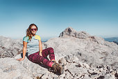 Caucasian woman with sunglasses, wearing a blue shirt and leggings hiking in the mountains. Adventurous woman hiking in the Alps alone. Scenic views on the mountains.