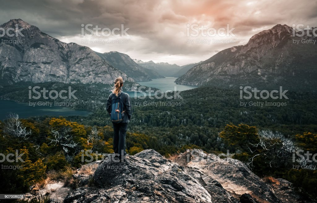 Woman hiker stands and enjoys valley view stock photo