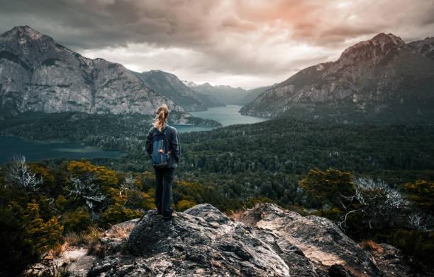 Caminante de la mujer se encuentra y goza de vistas al valle - foto de stock