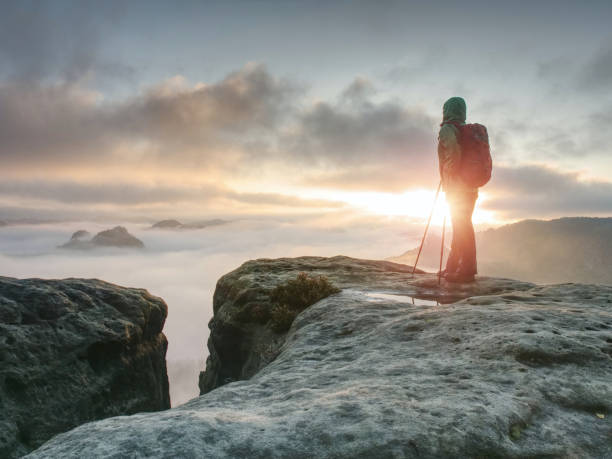 Woman hiker stop at the end of path on the edge stock photo