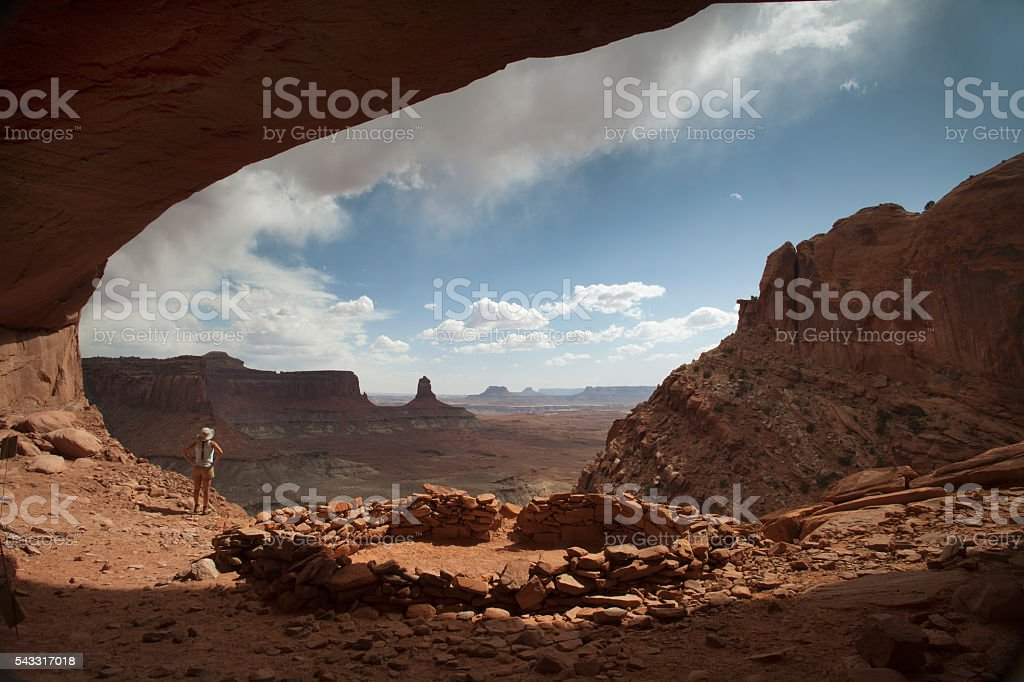 Woman hiker stormy alcove overlook Canyonlands National Park Utah stock photo