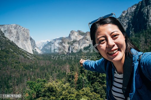 woman hiker looking camera taking selfie joyfully pointing finger to waterfall nature view. young asian backpacker cheerfully hiking in mountain in yosemite national park. female tourist travel.