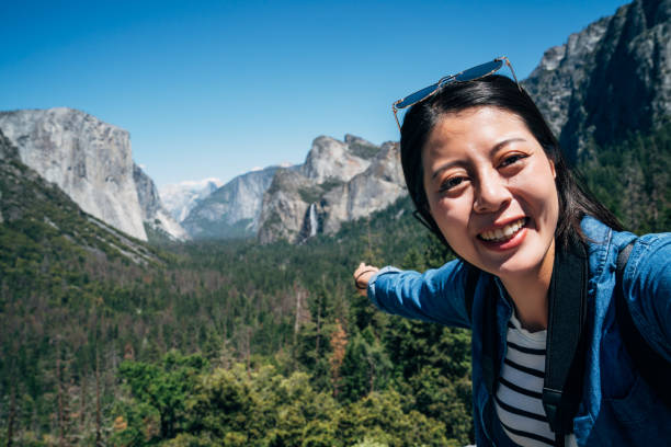 woman hiker taking selfie pointing to waterfall stock photo