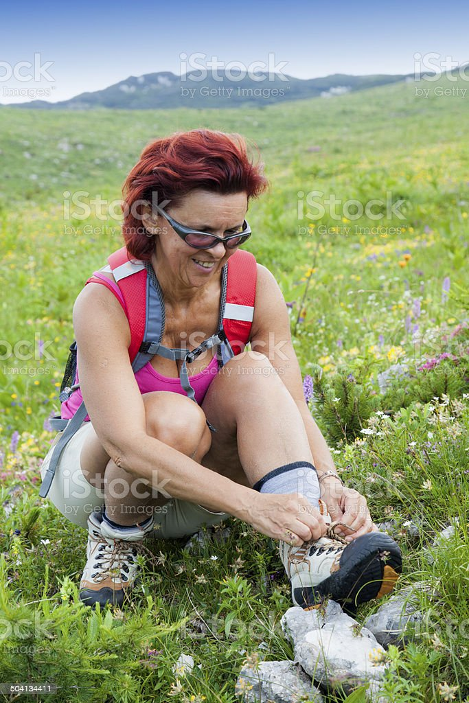 Woman hiker tying the shoelaces in mountains stock photo