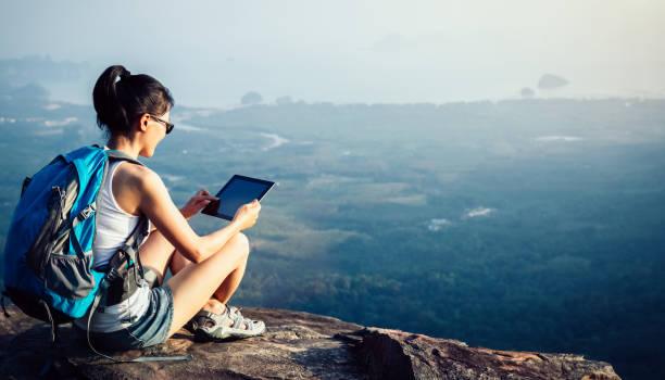 Wanderer nutzen digitales Tablet, das an der Bergspitze fotografiert wird – Foto