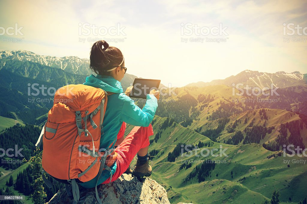 woman hiker use digital tablet taking photo on mountain peak foto royalty-free