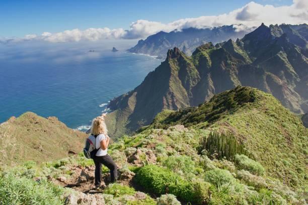randonneur de femme regardant la belle scène côtière. -tenerife, iles canaries, espagne. vue sur la côte ouest, montagne anaga - canari photos et images de collection