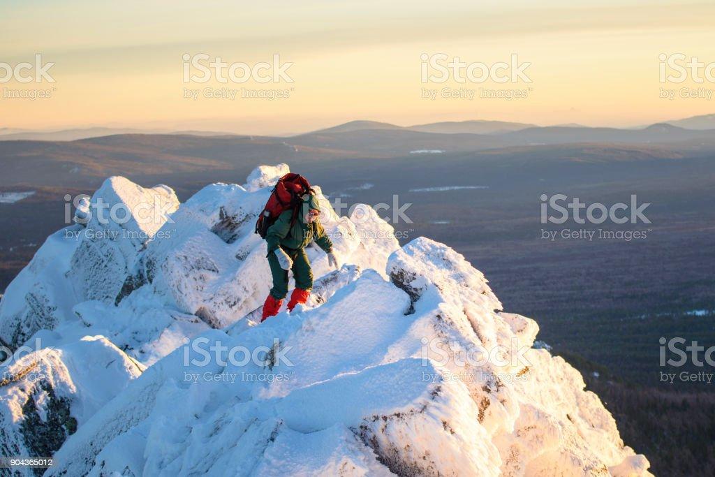 Excursionista de mujer con morral yendo a través de rocas y nieve en la cima de la montaña en el día de invierno. Héroe de la mujer y concepto de estilo de vida activo. - foto de stock
