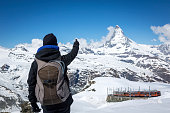 Woman Hiker with Backpack Pointing at Matterhorn mountain summit in Switzerland on a nice sunny day with clear sky.